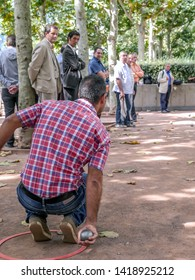 PARIS, FRANCE - AUGUST 29 2013: Traditional French boules game - one of players throwing bowl