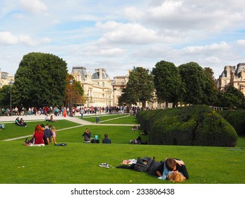 PARIS, FRANCE - AUGUST, 29, 2014. Park de Tuileries with on the background Musee du Louvre. In the grass are some people. Paris is a favorite traveling destination for a romantic trip.