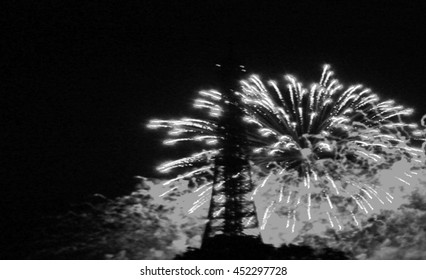 Paris, France. Blurred toned photo of fireworks near Eiffel Tower during celebrations of French national holiday (Bastille Day). Black and white.