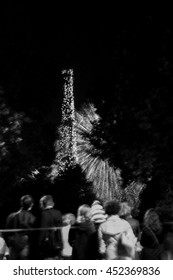 Paris, France. Blurred toned photo people watching fireworks near Eiffel Tower during celebrations of French national holiday (Bastille Day, on 14 July). Black and white.