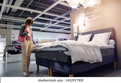 Paris, France - Circa 2019: Elegant French woman looking at bed duvet choosing furniture and bed linen mattress shopping for home bedroom renovation Ikea Swedish furniture store