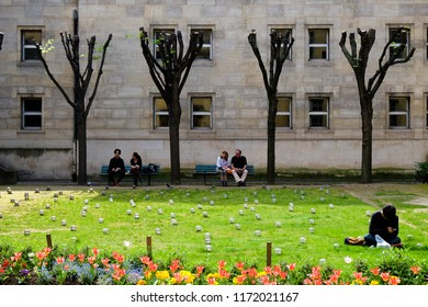 Paris, France - Circa April 2017: People sit in a park in the afternoon on a sunny day in the Marais district