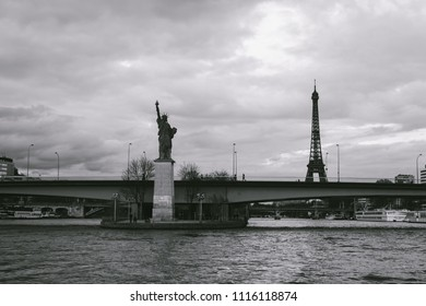 PARIS, FRANCE - CIRCA APRIL 2018: View of the Lady of Liberty statue, with the Eiffel Tower in the background, from a boat trip along the river Seine of Paris