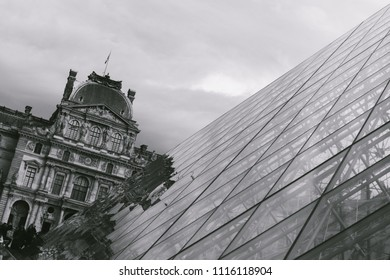 PARIS, FRANCE - CIRCA APRIL 2018: Exterior view of the glass pyramid and the original building of the Louvre museum in Paris