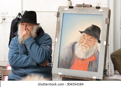 PARIS, FRANCE - CIRCA MAY 2011: Old Man in montmartresells painting of himslef