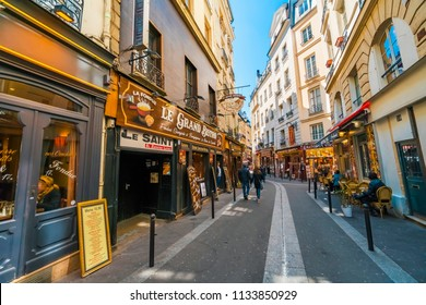 Paris, France - circa May, 2017: Latin Quarter. Narrow street of Paris among old traditional parisian houses and cafe