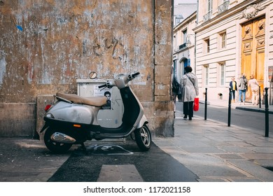 Paris, France - Circa November 2017: A scooter sits parked by a wall in the Marais district as people walk by