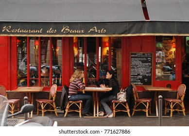 Paris, France – CIRCA October 2009: Two girls sit in bistro in Paris
