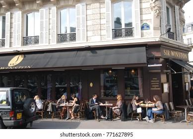 Paris, France – CIRCA October 2009: People sit in bistro in Paris