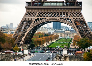Paris, France. Close view of famous Eiffel Tower and Champ de Mars with people and cars during the cloudy day in Paris. It most-visited paid monument in the world, even in autumn it's full of tourists