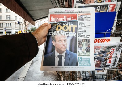 PARIS, FRANCE - DEC 10, 2018: Newspaper stand kiosk stand selling press with man buying Aujourd'hui Today newspaper featuring Emmanuel macon on the front page
