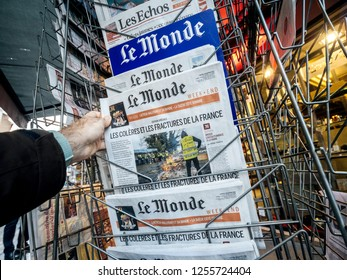 PARIS, FRANCE - DEC 10, 2018: Newspaper stand kiosk stand selling press with male hand buying latest Le monde featuring Gilets Jaunes Yellow Jackets movements on front cover
