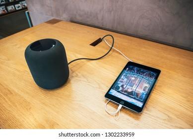 Paris, France - Dec 16, 2018: Apple Computers iPad tablet next to new Apple HomePod wireless speaker with Siri