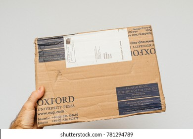 PARIS, FRANCE - DEC 18, 2017: Man holding Oxford Library Press cardboard parcel against white background