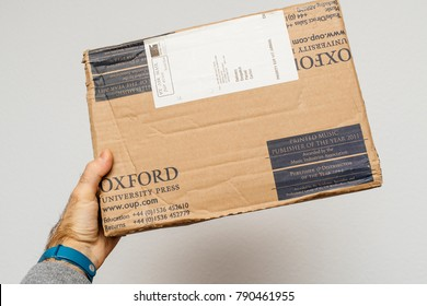 PARIS, FRANCE - DEC 18, 2017: Man golding against white background a parcel from the Oxford University Press containing books for High MBA PHD education