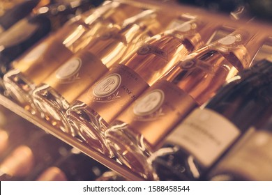 Paris, France - Dec 2019: Mood shot of brut Champagne sparkling wine Louis Roederer Cristal Rose 2009 and other wines in rack in restaurant. Close up wine bottles. Wine par excellence with a finesse.