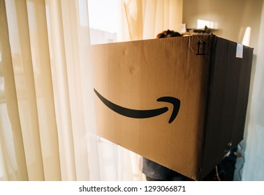 PARIS, FRANCE - DEC 25, 2018: Side view of woman holding large Amazon Prime parcel cardboard box on Christmas day with big huge gift inside