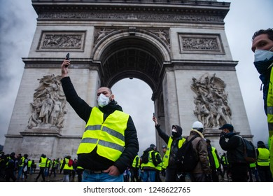 """Paris, France - December 01, 2018 : The Gilets Jaunes, or """"Yellow Vest"""", protestors clash with police while demonstrating against the government of President Macron near the Arc de Triomphe."""