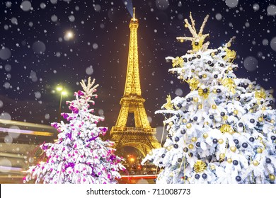 PARIS, FRANCE - DECEMBER 09, 2016: Eiffel Tower light performance show on the background of decorated Christmas trees in December by night. Travel Greeting Card with Christmas in Paris, France