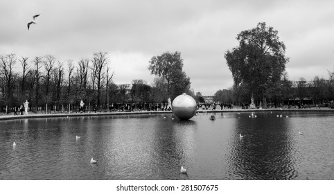 PARIS, FRANCE - DECEMBER 1, 2013: Golden Sphere by James Lee Byars is exhibited in Tuileries garden near Louvre museum.  Byars was specialized in installation sculpture and in performance art.