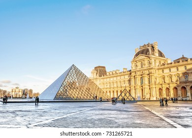 PARIS, FRANCE - DECEMBER 10,2016: View of famous Louvre museum and glass Pyramid at winter morning. Louvre Museum is most visited museums worldwide and one of major tourist attractions of Paris.