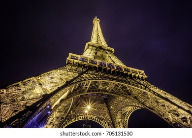 PARIS, FRANCE - DECEMBER 13, 2014: Shot close-up against Eiffel Tower is most visited monument in France and the most famous symbol of Paris at night