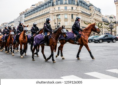 PARIS, FRANCE - December 15, 2018. Place Opera Garnier. Yellow vests demonstrate against the decline in purchasing power. A squadron of the police on horseback, goes to the Opéra Garnier.