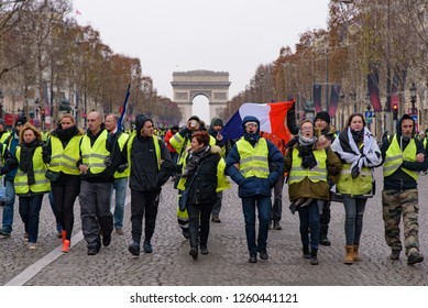 Paris / France - December 15 2018: 5th Yellow Vests demonstration (Gilets Jaunes) protesters against fuel tax, government, and French President Macron at Champs-Élysées and Arc de Triomphe