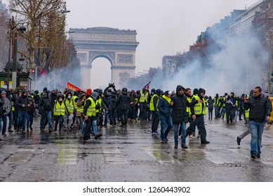 Paris / France - December 15 2018: Riot police firing tear gas at Yellow Vests demonstration (Gilets Jaunes) protesters against fuel tax, government, and French President Macron at Champs-Élysées
