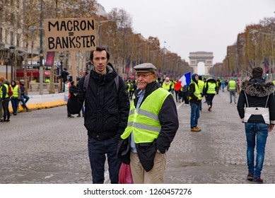 Paris / France - December 15 2018: 5th Yellow Vests demonstration (Gilets Jaunes) protesters against fuel tax, government, and French President Macron with slogan at Champs-Élysées