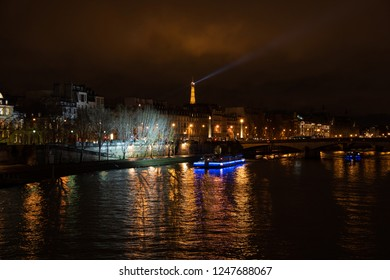 PARIS, FRANCE - DECEMBER 2, 2018:  Night view of illuminated Eiffel tower; touristic cruise ship at  Seine river sailing into beautiful lights reflection near Carrousel bridge and D'Orsay Museum.