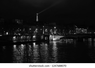 PARIS, FRANCE - DECEMBER 2, 2018:  Night view of illuminated Eiffel tower; touristic cruise ship at  Seine river sailing into lights reflection near Carrousel bridge and D'Orsay Museum. Black white.