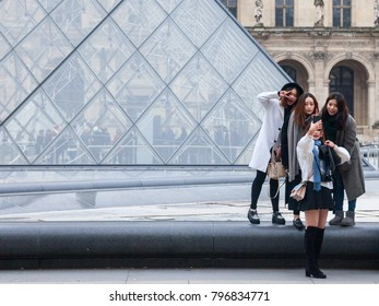 PARIS, FRANCE - DECEMBER 20, 2017: Chinese tourists taking selfie photos in front of the Louvre Pyramid. Louvre pyramid (Pyramide du Louvre) is one of the main attractions of Paris