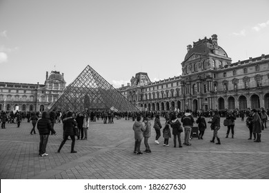PARIS, FRANCE - DECEMBER 26, 2013: Tourists taking photos in the main square of the Louvre Museum