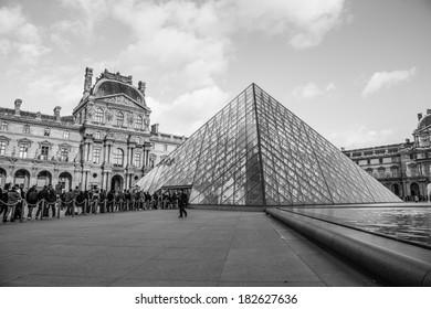 PARIS, FRANCE - DECEMBER 26, 2013: Tourists queuing to enter the Louvre Museum via the Pyramid entrance