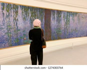 Paris, France- December 27, 2018: Woman in pink beret gazing at one of Claude Monet'a large waterlily paintings from the Nympheas series at the Musée de L'Orangerie
