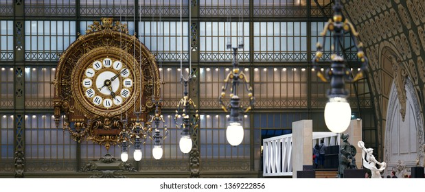 PARIS, FRANCE - December 28, 2018: Historic giant golden clock and iconic discharge lamps adorning the main hall of the Orsay Museum, formerly a 1900 railway station, on a wintry afternoon