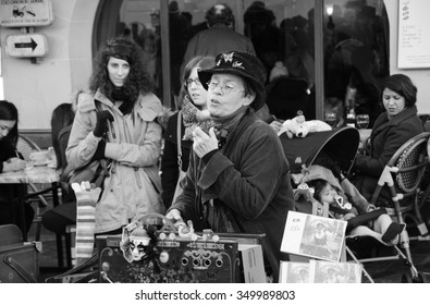 PARIS, FRANCE - DECEMBER 29, 2013:  Street artist Arlette Denis (Macadam Manivelle) singing and playing barrel organ at Montmartre.