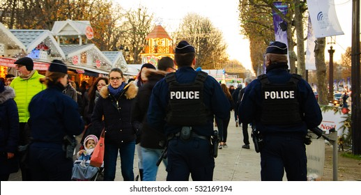 PARIS, FRANCE - DECEMBER 3, 2016: Policemen patrolling at Christmas market on avenue Champs-Elysees. France strengthened the measures to combat crime and terrorism. Selective focus on people in crowd.