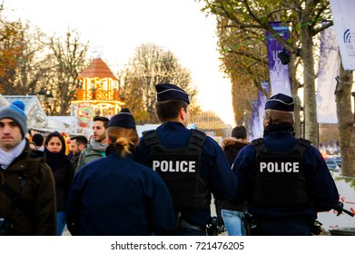 PARIS, FRANCE - DECEMBER 3, 2016: Policemen patrolling at Christmas market on avenue des Champs-Elysees at the evening. France strengthened the measures to combat crime and terrorism.