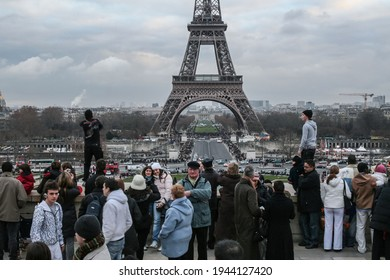 PARIS, FRANCE - DECEMBER 30, 2007: Selective blur on Eiffel tower, or Tour eiffel, seen from Trocadero with a crowd of people looking at two Tecktonik dancers performing electro dance.