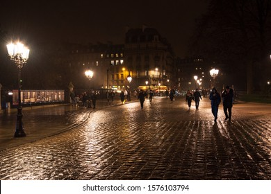 PARIS, FRANCE - DECEMBER 30, 2018:  View of Pont au Double (bridge leading to Notre Dame cathedral) and Seine river left bank at rainy evening.  Wet cobblestone sidewalk. Beautiful reflection.