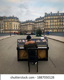 Paris, France December 30th 2018: A male pianist plays piano, plays music on a bridge, busking in Paris, France for tourists.