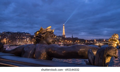 PARIS, FRANCE - DECEMBER 4, 2016 - View of a statue on Alexandre III bridge in Paris and the Eiffel tower at sunset