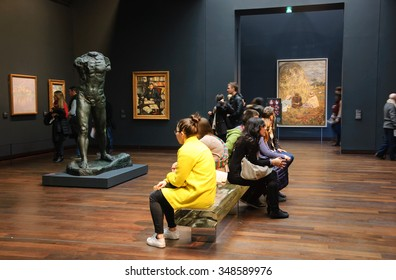 PARIS, FRANCE - DECEMBER 6, 2015: Visitors in permanent collection hall of Musee d'Orsay. Musee d'Orsay has the largest collection of impressionist and post-impressionist paintings in the world.