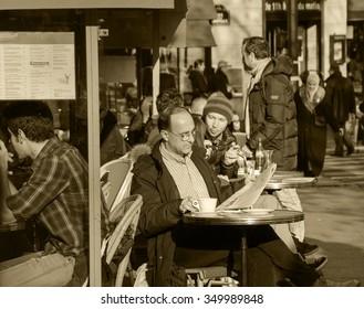 PARIS, FRANCE - DECEMBER 8, 2013: Parisians and tourists sit on terrace of  cafe at Place de la Bastille. Cafes in Paris appear to be an important cultural and socializing institutions.