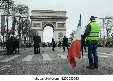 Paris, France - December 8, 2018: a protester holding a French flag stands in front of riot police at the Arc de Triomphe during a yellow vests (Gilets jaunes) protest on the Champs Elysees.