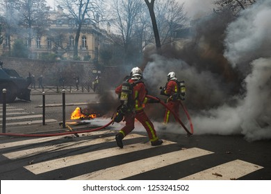 Paris, FRANCE - Decembrer 8 2018 : Firefighters try to put out a car fire during the riots of the Gilets jaunes (Yellows jackets) in Paris.