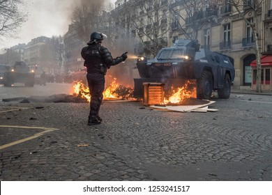 "Paris, FRANCE - Decembrer 8 2018 : Anti riot policeman with a VBRG an armoured vehicle used by the gendarmerie as an Internal security vehicle during the riots of the yellow vests ""gilets jaunes""."