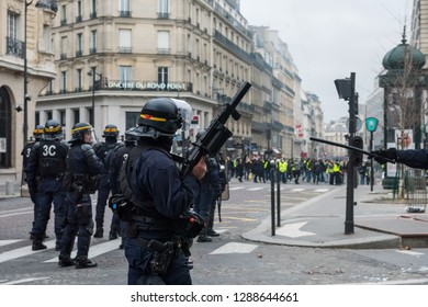 """Paris, FRANCE - Decembrer 8 2018 : Policeman from anti riot unit with a LBD flash-ball, control protesters Yellow Vest """"Gilets Jaunes"""" at Paris"""